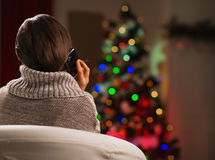 Woman calling mobile in front of Christmas tree Royalty Free Stock Photos