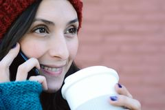 Woman calling on the mobile phone and holding a cup of coffee. Stock Photos