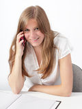 Woman calling in office. Happy congenial attractive young blond woman portrait sitting at office desk making a cellphone call smiling at camera Royalty Free Stock Photos
