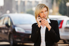 Blond fashion business woman calling on cell phone outdoor. Happy blond fashion business woman calling on cell phone on car parking Stock Photography