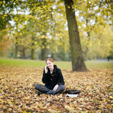 Woman Calling by Phone from an Autumn Park Royalty Free Stock Images