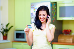 Woman calling by phone with credit card, at home Royalty Free Stock Images