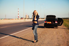 Fashion woman with broken car calling on cell phone Royalty Free Stock Photo