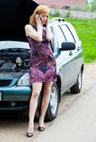 A woman is calling on a phone near the broken car Royalty Free Stock Photography