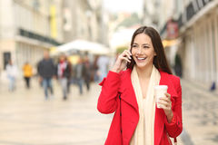 Woman calling on phone walking in the street Royalty Free Stock Photos