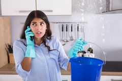 Woman Calling Plumber While Collecting Water stock photography