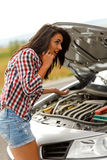 Woman calling service in front of broken car Royalty Free Stock Photo