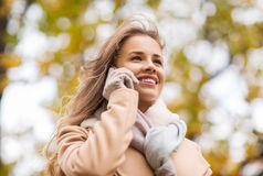 Woman calling on smartphone in autumn park Royalty Free Stock Photo