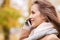 Woman calling on smartphone in autumn park Stock Images