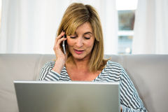 Woman calling someone. And looking at her laptop Stock Images