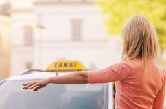 Woman calling taxi. Woman raising her arm to call a taxi stock images
