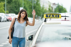Woman Calling For Taxi On Street. Young Woman Raising Arm To Hail Taxi On Street Royalty Free Stock Photo