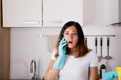 Woman Calling To Plumber For Water Leakage Problem royalty free stock images