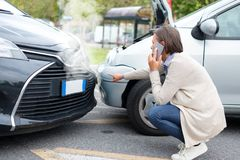 Woman calling to report car accident on the road stock images
