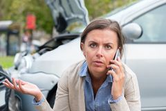 Woman calling to report car accident on the road stock photo