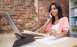 Woman calling and using laptop sitting at her desk Stock Photos