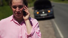 Woman Calls The Emergency Rescue Service. Young Frustrated Woman Calls The Emergency Rescue Service While Awaiting The Tow Truck For Her Car Broken On The Road stock footage