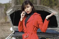 Woman calls for help. Young woman standing by her damaged car and calling for help Stock Photos