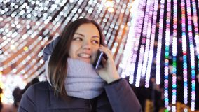 Woman calls relatives on Christmas Eve with congratulations, Christmas and New Year. `s celebration on the city Christmas tree stock footage