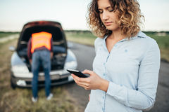 Woman calls to service, man repair broken car Royalty Free Stock Image