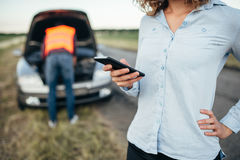 Woman calls to service, man repair broken car Royalty Free Stock Photo