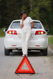 Woman calls to a service standing by a white car. Royalty Free Stock Photo