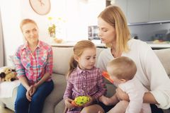 The woman came home and hugs her children. A babysitter is sitting next to them. The women came home and hugs her children. A babysitter is sitting next to them Royalty Free Stock Photo