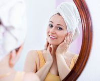Woman came from the shower and standing next to the mirror Stock Photography