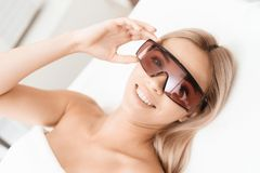 The woman came to the procedure of laser hair removal. She`s wearing red protective goggles. She is lying on the couch in a modern beauty salon royalty free stock images