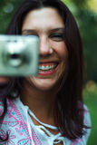 Woman with camera. Young woman outside taking a picure with a digital camera Stock Photos