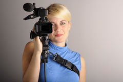 Woman with camera. Young blond woman hold video camera in hand Royalty Free Stock Photos