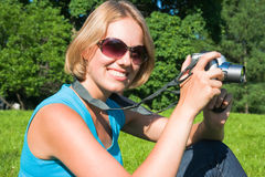 The woman with the camera. The beautiful blonde with the camera on the nature Stock Images