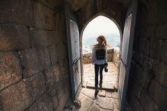 Woman with the camera explores a medieval castle fortress. Travel. Royalty Free Stock Photos