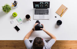 Woman with camera and laptop at office table Stock Images