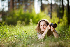 A woman with a camera lying on the grass in the park Royalty Free Stock Images