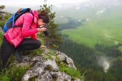 Woman with camera making photo on mountain peak Stock Image