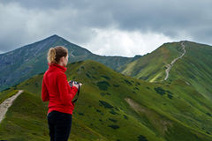 Woman with camera on a mountain path Royalty Free Stock Photo