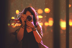 Woman with camera on night city background Stock Image