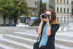 Woman with a camera photographs the city Royalty Free Stock Images