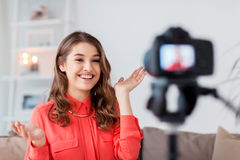 Woman with camera recording video at home. Blogging, technology, videoblog, mass media and people concept - happy smiling woman or blogger with camera recording royalty free stock photography