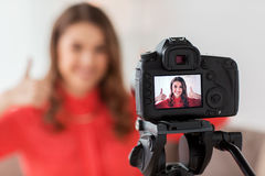 Woman with camera recording video at home. Blogging, technology, videoblog, mass media and people concept - happy smiling woman or blogger with camera recording Stock Photography
