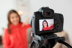 Woman with camera recording video at home. Blogging, technology, videoblog, mass media and people concept - happy smiling woman or blogger with camera recording Royalty Free Stock Photos
