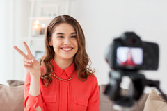 Woman with camera recording video at home. Blogging, technology, videoblog, mass media and people concept - happy smiling woman or blogger with camera recording Stock Photo