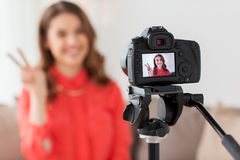 Woman with camera recording video at home. Blogging, technology, videoblog, mass media and people concept - happy smiling woman or blogger with camera recording Royalty Free Stock Images