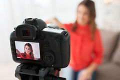 Woman with camera recording video at home. Blogging, technology, videoblog, mass media and people concept - happy smiling woman or blogger with camera recording Stock Images