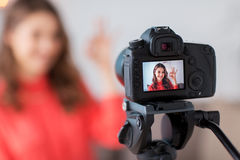 Woman with camera recording video at home. Blogging, technology, videoblog, mass media and people concept - happy smiling woman or blogger with camera recording Royalty Free Stock Image