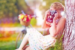 Woman with camera relaxing after bicycle ride Stock Image