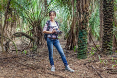 Woman with camera stands in the forest Royalty Free Stock Images