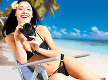 Woman with a camera taking photos on beach Royalty Free Stock Images