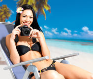 Woman with a camera taking photos on beach Stock Photos
